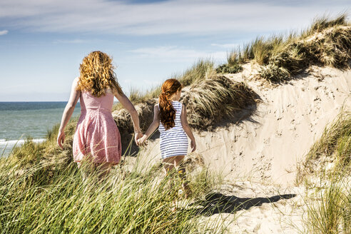 Netherlands, Zandvoort, mother and daughter walking in beach dunes - FMKF04367