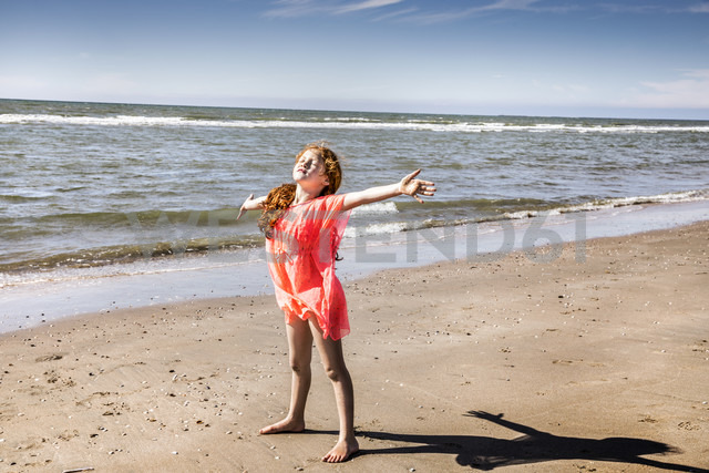 Netherlands, Zandvoort, girl standing on the beach with outstretched arms - FMKF04373