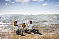 Netherlands, Zandvoort, family sitting on chairs in the sea - FMKF04376