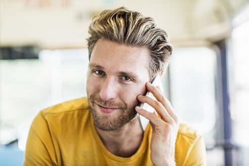 Portrait of smiling man on cell phone - FMKF04379