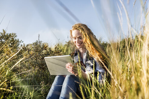 Netherlands, Zandvoort, smiling woman sitting in dunes with tablet - FMKF04382