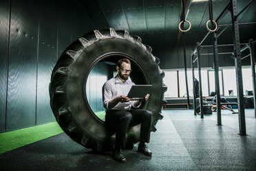 Businessman sitting in truck tire in a gym, using laptop - JOSF01319