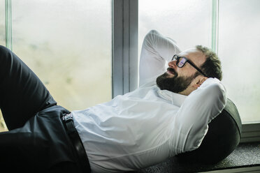 Businessman lying on window sill, taking a break - JOSF01346