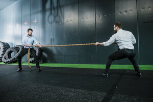 Two businessmen in gym doing tug of war - JOSF01361