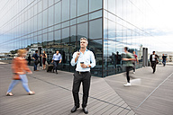Businessman holding cup of coffee, people walking around him - ZEF14295