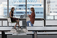 Businesswoman talking to colleague in modern office - ZEF14298