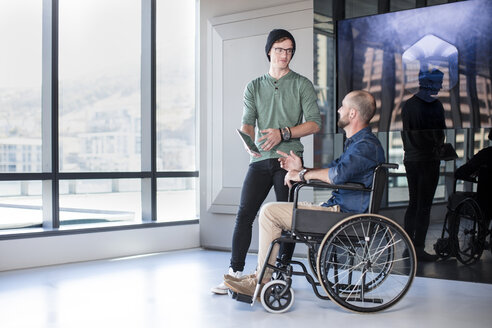 Man talking to handicapped colleague in wheelchair - ZEF14313