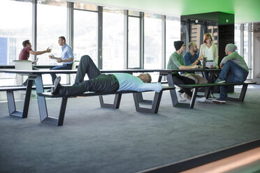 Businessman relaxing on a bench in modern open space office - ZEF14316