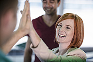 Happy business people high-fiving in office - ZEF14319