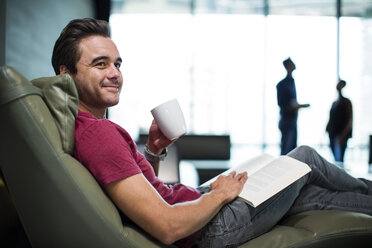 Man in office sitting in armchair, reading a book - ZEF14337