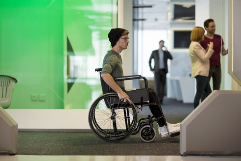 Young man in wheelchair listening to  music in office - ZEF14346