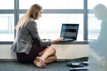 Businesswoman sitting on floor, using laptop - ZEF14349