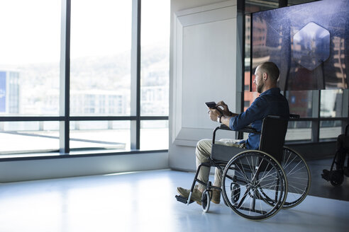 Man in wheelchair looking out of window in office, using tablet - ZEF14352
