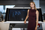 Businesswoman standing in front of communication screen - ZEF14355