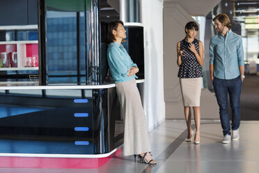Exhausted businesswoman leaning on wall in busy office corridor - ZEF14397