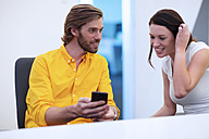 Businesspeople sitting in office, talking, using smartphone - ZEF14406