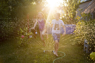 Brother and sister having fun with lawn sprinkler in the garden - SARF03349