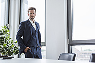 Portrait of businessman standing in his office - DIGF02675