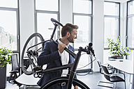 Smiling businessman with bicycle on his shoulder in the office - DIGF02678