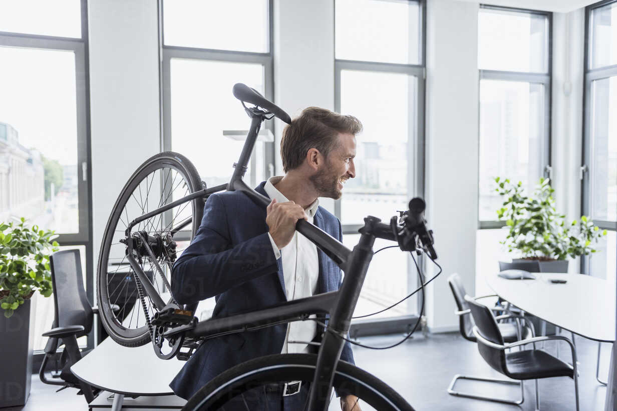 Smiling businessman with bicycle on his shoulder in the office - DIGF02678 - Daniel Ingold/Westend61