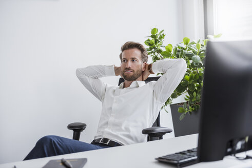 Portrait of businessman relaxing at desk in his office - DIGF02690