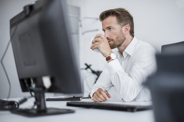 Portrait of serious businessman sitting at desk in the office drinking coffee - DIGF02696