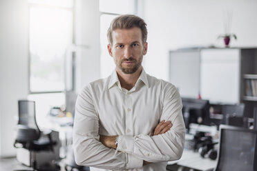 Portrait of serious businessman with arms crossed in the office - DIGF02699