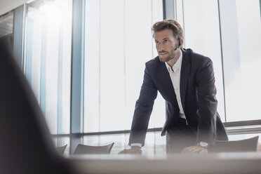 Portrait of businessman with bluetooth headset standing in conference room - DIGF02705
