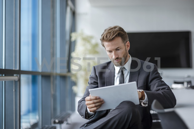 Businessman sitting in conference room using tablet - DIGF02711