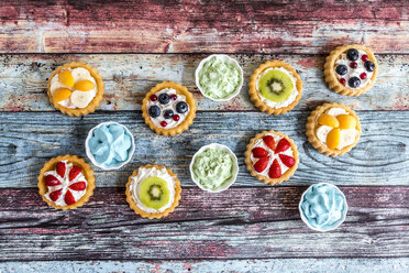 Mini pies with whipped cream garnished with different fruits - SARF03354