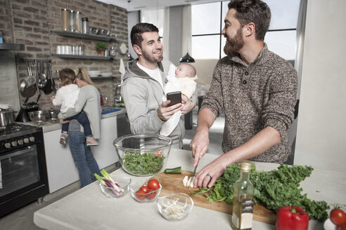 Family and friends preparing a healthy meal in kitchen - ZEF14411