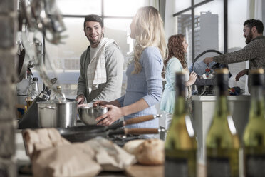 Couple preparing food in kitchen with family in the background - ZEF14468