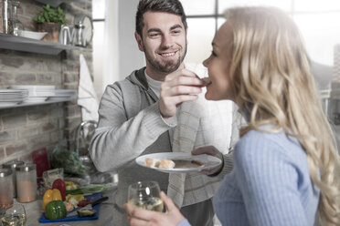 Couple tasting food together in kitchen - ZEF14474