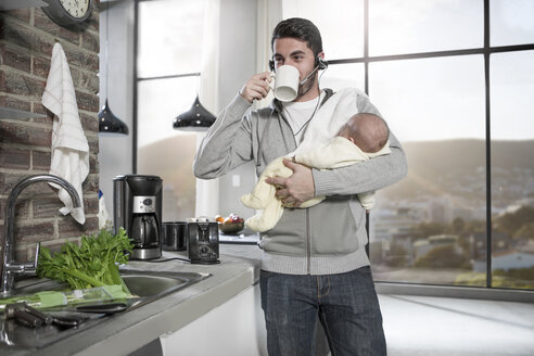 Father with headset drinking coffee in kitchen holding baby - ZEF14480