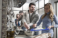 Couple cooking for family and friends in kitchen - ZEF14489
