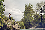 Slovenia, man fly fishing in Soca river standing on a rock - BMAF00314