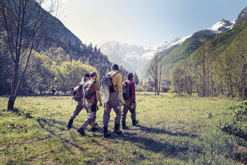 Slovenia, Bovec, four anglers walking on meadow towards Soca river - BMAF00332