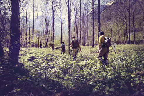 Slovenia, Bovec, three anglers walking in forest towards Soca river - BMAF00335