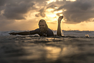 Indonesia, Bali, surfer in the ocean at sunrise - KNTF00876