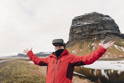 Iceland, man wearing Virtual Reality Glasses in nature - RAEF01903