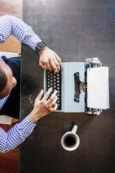 Young man at desk using typewriter - GIOF03135
