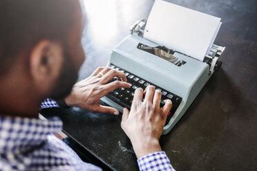 Close-up of man at desk using typewriter - GIOF03138