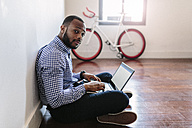 Man using laptop sitting on wooden floor with bicycle in background - GIOF03144
