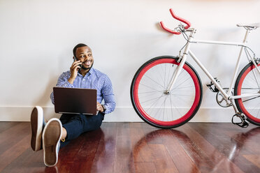 Smiling man on cell phone sitting on wooden floor with bicycle next to him - GIOF03147