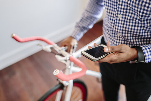 Close-up of man checking the phone while holding a bike indoors - GIOF03150