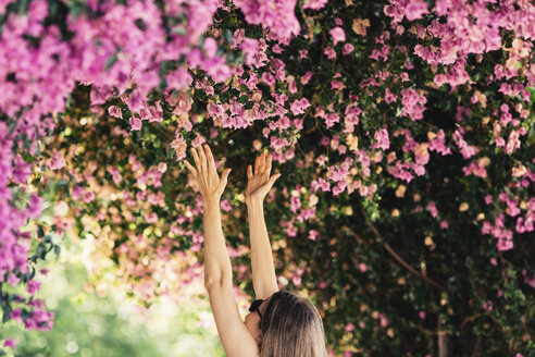 Woman reaching for pink blossoms in park - JPF00270