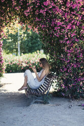 Woman with cell phone sitting on bench in park under pink blossoms - JPF00273