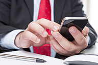 Businessman sitting at desk text messaging, close-up - PUF00671