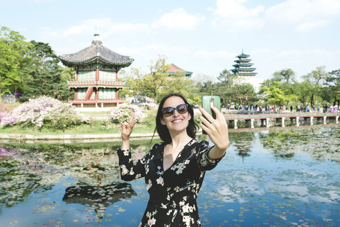 South Korea, Seoul, Woman taking a selfie with smartphone at Gyeongbokgung Palace - GEMF01765