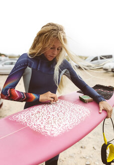 Spain, Aviles, young surfer preparing her surfboard - MGOF03540
